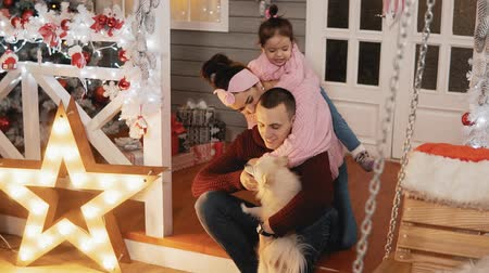 Happy family of mother, father, daughter and dog have fun at Christmas porch Stock mozgókép