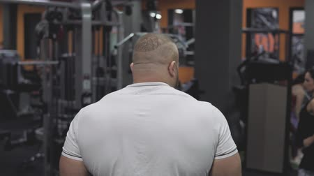 Follow-up shot of muscular man entering gym in slow motion Stock mozgókép