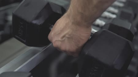 Closeup of male hand taking dumbbells, strength training equipment in gym