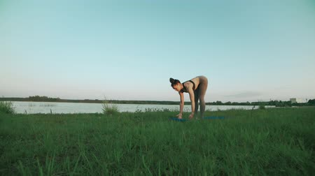 Young girl on blue yoga mat in quiet scenery. Woman doing yoga
