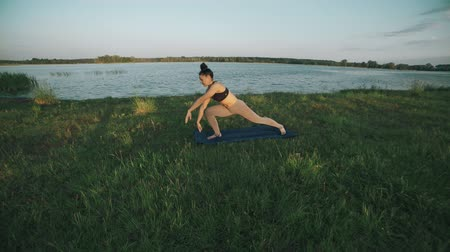 Beautiful woman practicing yoga in morning. Girl doing yoga moves on green grass