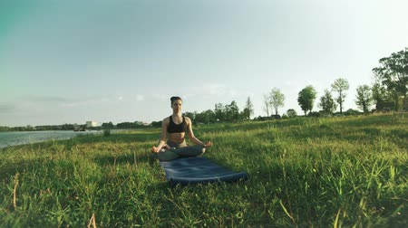 Pretty girl in lotus position at sunrise. Woman doing yoga in morning at lake