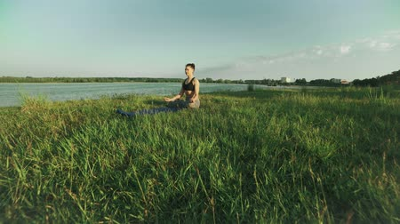 Young girl in lotus position at sunrise. Woman doing yoga in morning at lake Vídeos