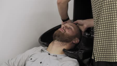Barber washing hair to bearded man in male salon. Hairdresser wash male head Stock mozgókép