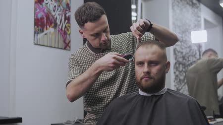 Styling with electric trimmer. Professional hairdresser cutting hair in slo-mo