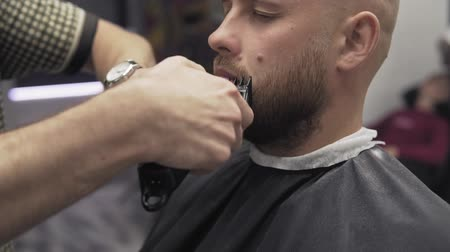 Barber shaving beard with electric razor and comb salon. Barber trimming beard
