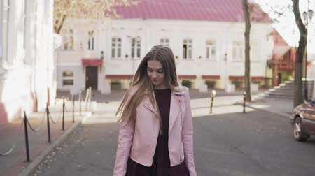 hopeful : Beautiful girl in pink jacket walking at city and smiling at camera in slow-mo