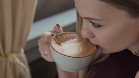 to be alone : Attractive girl smelling the aroma of coffee and relaxing in cafe.