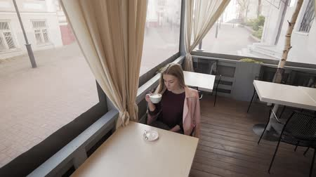 to be alone : Attractive girl drinking coffee in cafe during break. Woman with cup of coffee Stock Footage