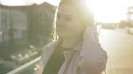Close-up Portrait of pretty woman with long hair smiling in city at sunrise
