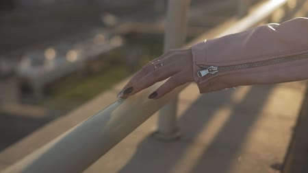 Close up of woman hands on metalic railing in slow motion