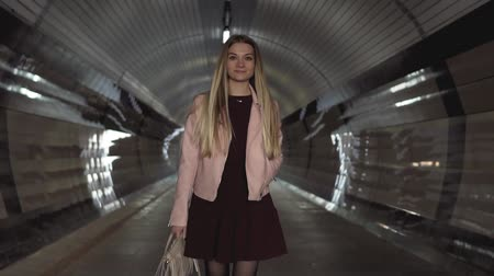 Charming young girl walks through tunnel in pink jacket at sunset