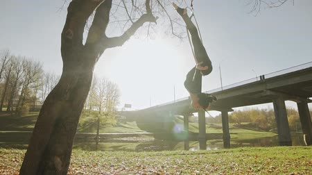 abroncs : Flexible brunette hanging in ring for aerial acrobatic at sunrise in slow motion