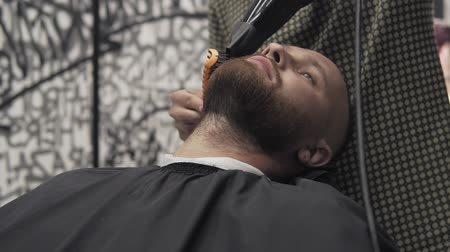 barber equipment : Close up of male barber trimming beard with shaver. Professional shaving