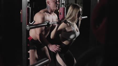 pumping : Fitness woman doing squats with barbell in dark gym with trainer in slow motion