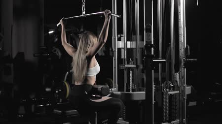 gewichtheffen : Woman training with weight-lifting training machine in slow motion in dark gym Stockvideo