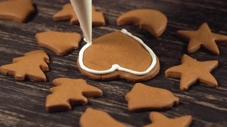 speculaas : Close up garnishing homemade gingerbread heart. Decoration of Christmas cookies.