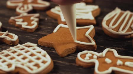 garnishing : Close up garnishing homemade gingerbread star. Decoration of Christmas cookies. Stock Footage