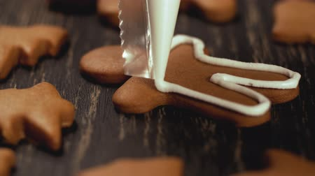 kurabiye : Close up garnishing gingerbread men. Decoration process of Christmas cookies.