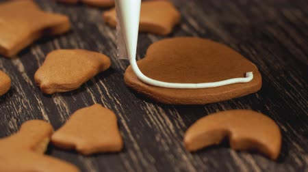 застекленный : Decoration of Christmas cookies. Close up garnishing homemade gingerbread heart Стоковые видеозаписи