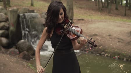 hegedűművész : Beautiful violinist plays with inspiration. Girl playing violin in forest