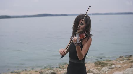 mozart : Beautiful girl in black dress plays violin at sea background. Art concept in 4k