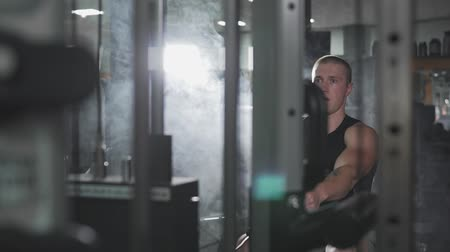 ağır çekimli : Man workout on fitness machine in dark gym with copy space at left Stok Video