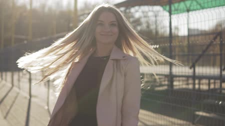 hopeful : Smiling blonde woman looking at camera outdoor at sunset in slow motion