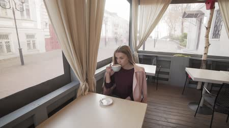 to be alone : Cute girl drinking coffee in cafe during break. Young woman with cup of coffee