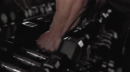 amatőr : Closeup of male hand taking dumbbells, strength training equipment in gym