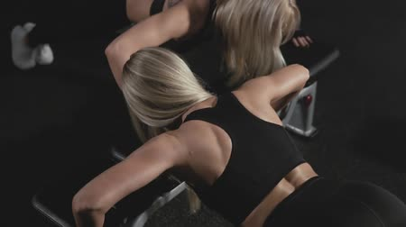 motywacja : Two sporty blonde girls doing push ups in dark smoky gym in slow motion Wideo