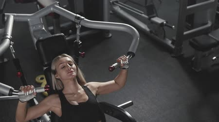 weightlifting : Athletic young woman working out on fitness exercise equipment at gym