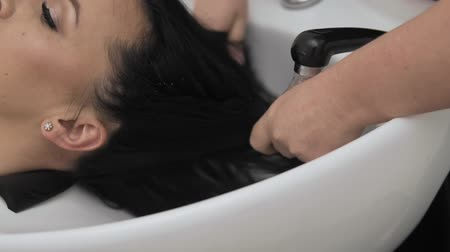 conditioner : Hairdresser in gloves washing brunette girl hair over sink in beauty shop. Stock Footage