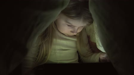 sigilo : Little girl with tablet under blanket. Kid at night with tablet. Girl in bedroom