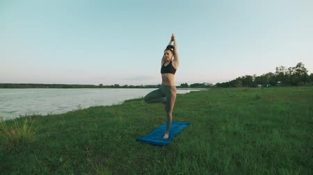 rajstopy : Beautiful young girl wearing sports clothes black top and gray tights doing yoga in morning at lake, sun salutation on blue yoga mat in quiet scenery. Healthy lifestyle concept with copyspace