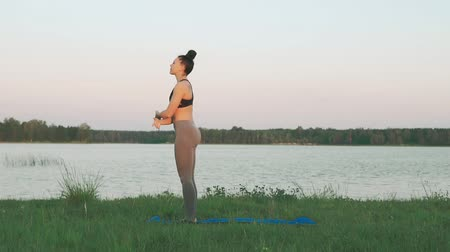 punčocháče : Beautiful young girl wearing sports clothes black top and gray tights doing yoga in morning at lake, sun salutation on blue yoga mat in quiet scenery. Healthy lifestyle concept with copyspace