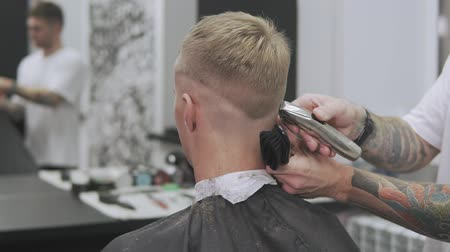 ustalık : Male haircut with electric razor. Medium shot of hair trimmer hairstyle. Man hairdressing with electric shaver. Styling with electric trimmer. Professional hairdresser cutting hair with hair clipper Stok Video