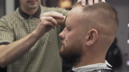 beard trim : Male barber trimming beard with shaver. Barber shaving beard with electric razor and comb in male salon Stock Footage