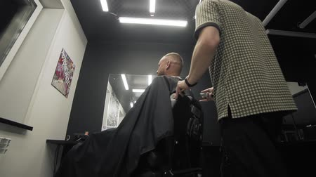hairstyliste : Professional shaving bearded man in slow motion. Barber shaving beard with electric razor and comb in male salon. Male barber trimming beard with shaver. Wide angle