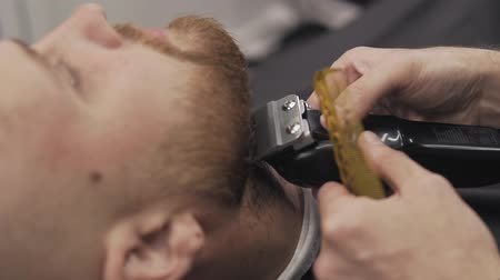 beard trim : Close up of male barber trimming beard with shaver. Barber shaving beard with electric razor and comb in male salon. Professional shaving bearded man in slow motion