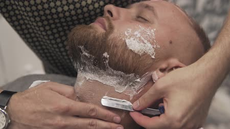 férfias : Barber shaving bearded man with straight razor in male salon. Male skin care and beard style concept in slow motion
