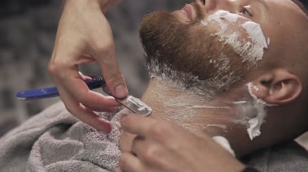 navalha : Barber shaving bearded man with straight razor in barbershop. Male skin care and beard style concept. Close up shaving razor to hipster beard in barber shop