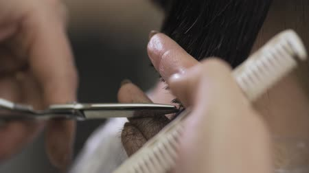 taberna : Female hairdresser hold in hand between fingers lock of hair, comb and scissors in slow motion. Close up. Trim tips of hair by scissors. Beauty salon Vídeos