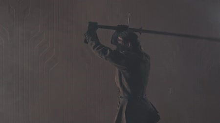 中世の : Medieval warrior training with two-handed sword indoors in slow motion. Medium shot