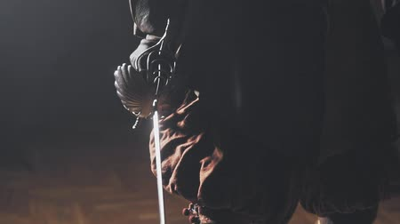 legionary : Medieval warrior with sword indoors in slow motion. Close-up.