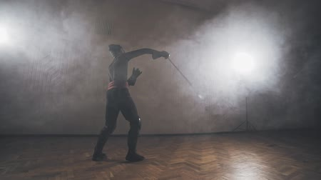 legionary : Medieval warrior training with sword indoors in slow motion.