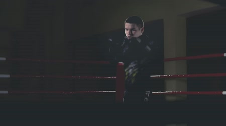 chránit : Kickboxer training in dark boxing ring. Boxer boxing as exercise for the fight. Sportsman boxing in slow motion with copy space