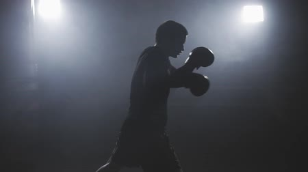 füstös : Muay thai fighter punching in smoky studio. Kickboxer training in low light gym in slow motion. Silhouette on dark background