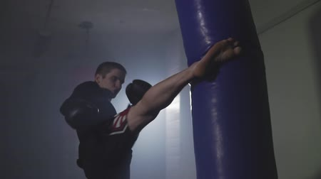 punching bag : Kickboxer punching in smoky studio. Muay thai fighter training with punching bag on dark background