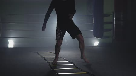 fight club : Kickboxer training in smoky studio. Muay thai fighter training legs in slow motion Stock Footage